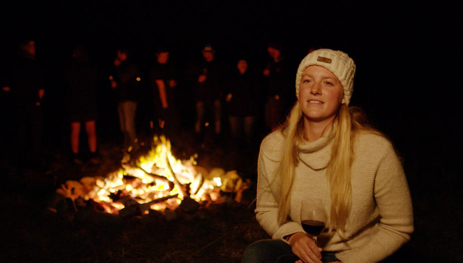 Jess sitting by bonfire
